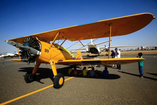 People look at the vintage Boeing-Stearman Model 75 biplane as it sits on the runway on November 20, 2016 in Khartoum airport during the Vintage Air Rally (VAR). A dozen biplanes from the 1920s and 1930s are flying 8,000 miles from Crete to Cape Town in a vintage aviation rally that harks back to the early days of air travel. The pilots will fly along the Nile from Cairo to Khartoum, past the highlands of Ethiopia, down through East Africa past Mount Kilimanjaro, over Victoria Falls, and will end in South Africa. It is the first aviation rally to be granted permission to land at Egypt's Giza pyramids in 50 years, and will put on Sudan's first air show. (Photo by Ashraf Shazly/AFP Photo)