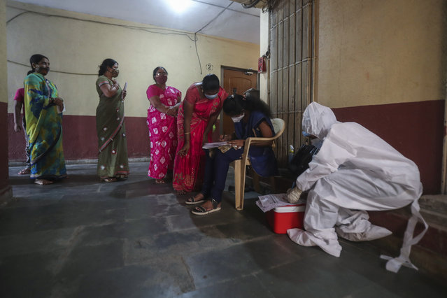 People register themselves to get tested during a door-to-door screening for COVID-19 people at Dharavi, one of Asia's largest slums, in Mumbai, India, Wednesday, March 17, 2021. (Photo by Rafiq Maqbool/AP Photo)