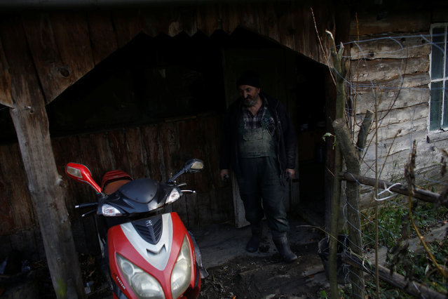 Charcoal burner Zygmunt Furdygiel looks at his scooter in front of his hut at a charcoal making site in the forest of Bieszczady Mountains, near the village of Baligrod, Poland November 5, 2016. (Photo by Kacper Pempel/Reuters)