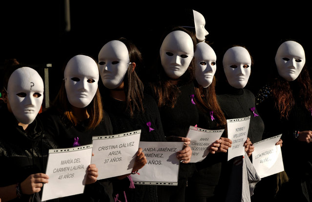 Gender studies students wear masks and hold signs bearing names and ages during a performance to commemorate victims of gender violence, during the U.N. International Day for the Elimination of Violence against Women, in Oviedo, Spain November 25, 2016. (Photo by Eloy Alonso/Reuters)
