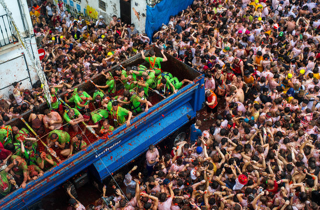 Revellers throw tomatoes while participating the annual Tomatina festival on August 28, 2013 in Bunol, Spain. An estimated 20,000 people threw 130 tons of ripe tomatoes in the world's biggest tomato fight held annually in this Spanish Mediterranean town. (Photo by David Ramos/Getty Images)