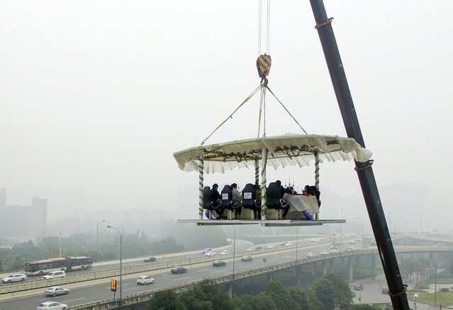 People dine while lifted about 30 meters above ground, as part of a shopping mall's promotional event, during a hazy day in Chengdu, Sichuan province, China December 31, 2015. (Photo by Reuters/Stringer)