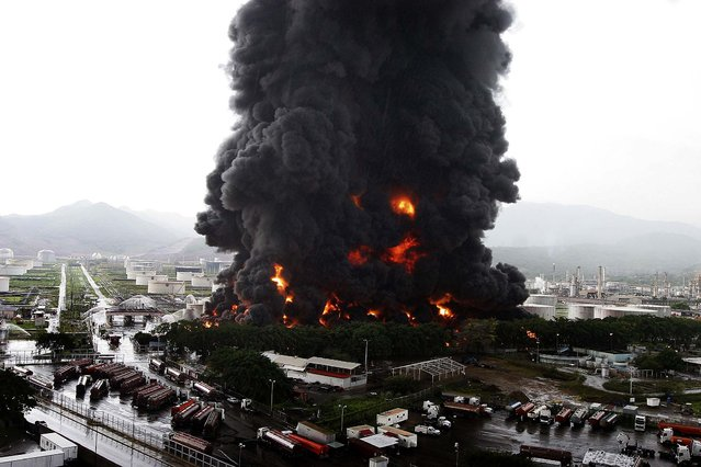 Firefighters try to extinguish a fire at an oil refinery in Puerto La Cruz, Venezuela, on August 11, 2013. Lightning set fire to a storage tank at the refinery, and residents were moved out of the immediate area. (Photo by Reuters)