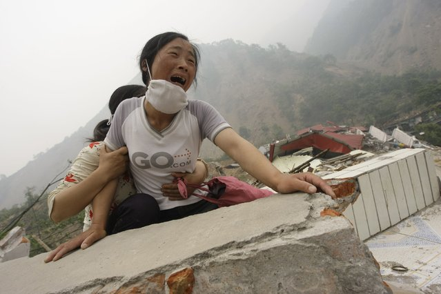 A woman cries as she cannot find her 4-year-old daughter and husband on the top of the ruins of a destroyed school in earthquake-hit Beichuan county, Sichuan province in this May 17, 2008 file photo. Jason Lee:  It was the fifth day since the deadly Sichuan Earthquake shook southwestern China. People were still looking for survivors in the ruins of Beichuan county, one of the worst-hit areas. (Photo by Jason Lee/Reuters)