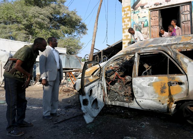 Somali security agents inspect a charred car after an explosion that they said left three wounded in Mogadishu January 10, 2016. (Photo by Feisal Omar/Reuters)