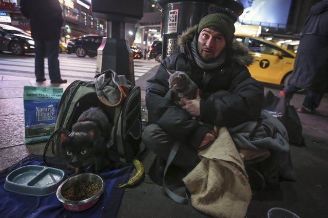 Keith Rosario sits with his cats Storm and Molly (L) as he panhandles on the street outside Pennsylvania Station in the Manhattan borough of New York, January 5, 2016. (Photo by Carlo Allegri/Reuters)