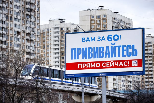 """A monorail car rolls near a gait billboard reading """"You're over 60! Get vaccinated immediately!"""" in Moscow, Russia, Sunday, April 4, 2021. To boost the demand, officials in Moscow this week started offering 1,000-ruble ($13) coupons to people over 60 for getting vaccinated. So far, the incentive hasn't elicited a lot of enthusiasm among elderly Muscovites. While some told the AP the initiative was helpful for those living off a relatively small pension, others complained about difficulties registering online to get the coupons or finding grocery stores where they could be used. (Photo by Alexander Zemlianichenko/AP Photo)"""