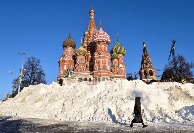 A woman walks past a snow heap at Red Square, with St. Basil's Cathedral seen in the background, as temperatures dropped to -13 degrees Celsius in Moscow on December 7, 2016. (Photo by Natalia Kolesnikova/AFP Photo)