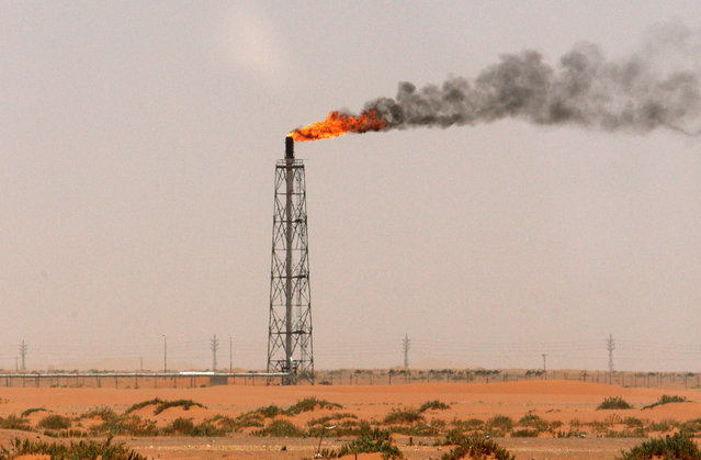 A gas flame is seen in the desert near the Khurais oilfield, about 160 km (99 miles) from Riyadh, June 23, 2008. (Photo by Ali Jarekji/Reuters)