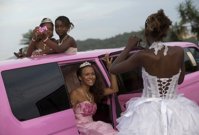 In this November 8, 2012, file photo, girls turning 15 pose in their gowns for photos inside a pink limousine before their debutante ball, organized by the Peacemaker Police Unit program in the Mangueira favela, or shantytown, in Rio de Janeiro, Brazil. The debutante ball marks girls' transition from childhood to adulthood and is common in Brazil and other Latin American countries. (Photo by Silvia Izquierdo/AP Photo)