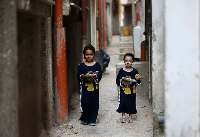 Girls walk in an alley in Balata refugee camp near the West Bank city of Nablus, during the fasting month of Ramadan, on April 20, 2021. (Photo by Chine Nouvelle/SIPA Press/Rex Features/Shutterstock)