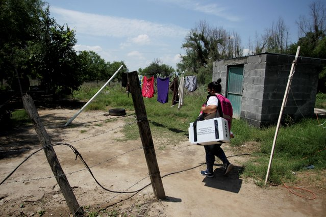 A worker of the National Electoral Institute (INE) carries voting materials while delivering to a polling station ahead of the mid-term elections on June 6, in Mamulique, on the outskirts of Monterrey, Mexico on June 2, 2021. (Photo by Daniel Becerril/Reuters)