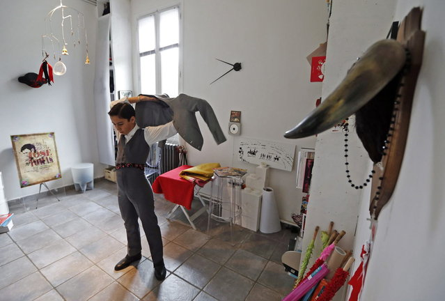 Solal, a twelve-year-old toreador apprentice, dresses before a beginner's bullfight (becerrada) at his home in Nimes, October 5, 2013. Since 1983, the French Tauromachy Centre in Nimes has trained some 1,000 youths in the art of bullfighting. Twenty of them have gone on to become professional matadors, facing fighting bulls in the arena. Twice a week, students take courses with a matador to learn the movements and gestures of the bullfighter in the ring, but without an animal present. Students train with calves in the surrounding fields during spring, and regularly participate in beginner's bullfights (becerradas) without killing calves. Solal has been taking courses for three years and Nino, for just a year now. Both are normally enrolled in French public schools, but have one thought in mind – bullfighting. They share a passion linked to the city of Nimes, famous for its ferias and bullring. (Photo by Jean-Paul Pelissier/Reuters)