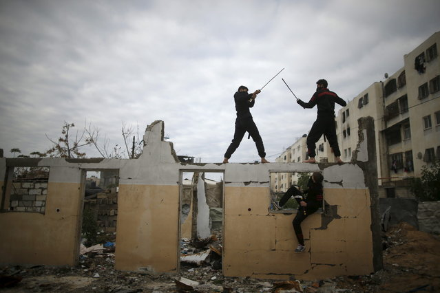 Palestinian youths fight with swords as they demonstrate their ninja-style skills for a photographer at the ruins of a house, that was destroyed in the 2014 war, in the northern Gaza Strip January 29, 2016. (Photo by Mohammed Salem/Reuters)