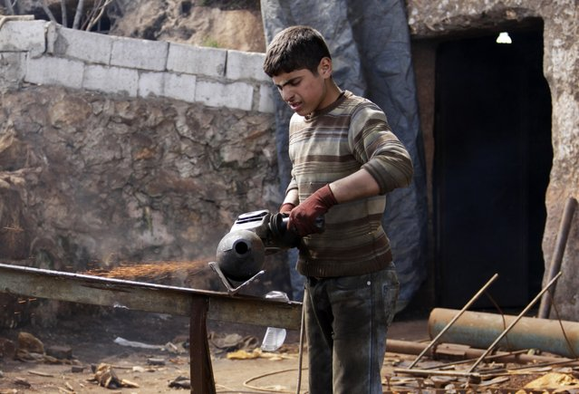 A man works on a mortar shell at a weapon factory operated by rebel fighters from Suqour al-Sham Brigade in Idlib countryside March 18, 2015. (Photo by Mohamad Bayoush/Reuters)