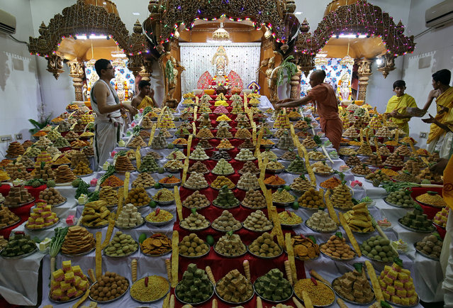 """A priest arranges sweets kept inside a temple as offerings by Hindu devotees as part of a ritual to mark """"Annakut"""" festival during Diwali, the Hindu festival of lights, in Ahmedabad, India, November 7, 2018. (Photo by Amit Dave/Reuters)"""
