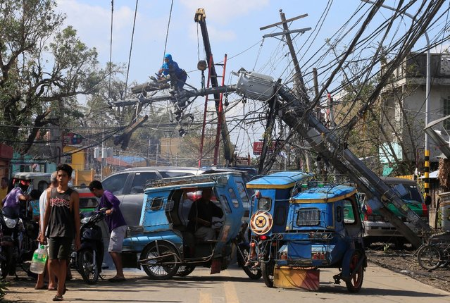 A worker fixes an electric post after it was damaged during Typhoon Nock-ten, Iriga city, Camarines Sur, central Philippines December 27, 2016. (Photo by Romeo Ranoco/Reuters)