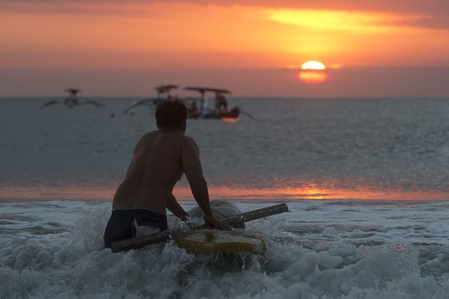 A man takes his paddle board for fishing at Kuta beach during the sunset in Bali, Indonesia, Wednesday, May 12, 2021. (Photo by Firdia Lisnawati/AP Photo)