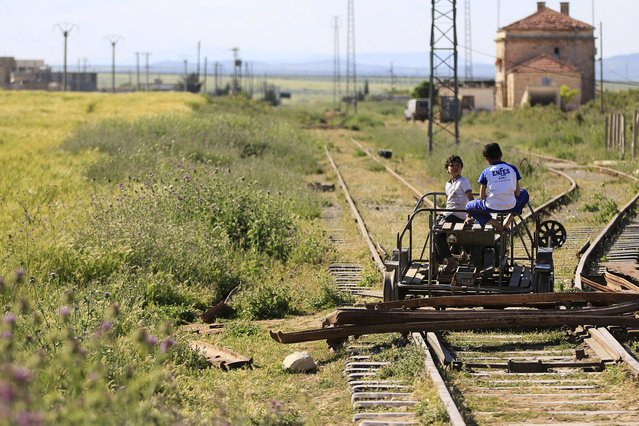 Children play on the railway tracks at Tell i-Refat train station in the northern countryside of Aleppo May 6, 2015. The station that connects the district of Aleppo with Turkey is out of service since nearly three years due to the conflict in the country. (Photo by Hamid Khatib/Reuters)