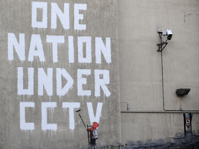 Street graffiti by Banksy on a wall next to a CCTV camera in central London in 2008. (Photo by Toby Melville/Reuters)