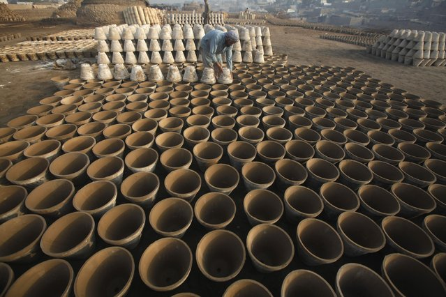 A labourer arranges clay pots for drying at a small traditional factory on the outskirts of Karachi February 19, 2015. (Photo by Athar Hussain/Reuters)