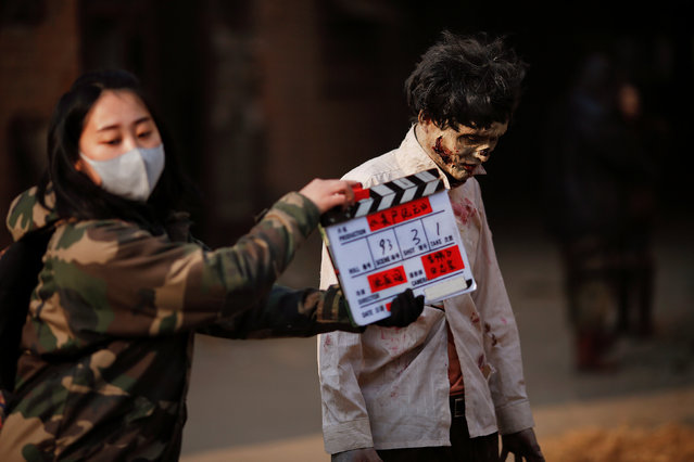 """A crew member snaps the clapperboard at the set of the post-apocalyptic movie Zombie Era at an abandoned factory complex in Langfang, Hebei province, China December 16, 2016. The post-apocalyptic thriller """"Zombie Era"""" is the latest domestically-produced movie destined for a growing online audience in China. Demand for video streaming of movies and TV shows has opened the door to a new generation of directors like 27-year-old Shen Chenyan. The former cinematographer, who oversees 100 cast members and crew on the """"Zombie Era"""" set in an abandoned factory near the capital Beijing, said he would have waited years for the chance to direct a traditional cinema release. """"The quality and quantity of online movies are going up, so it's a great opportunity to try out a few of my own thoughts and to fulfil my intention of becoming a film director"""". Although China is the world's second largest movie market, the outlook for cinema operators is cloudy after its box-office ended 2016 with its smallest growth in a decade, up just 3.7 percent on the year, at 45.7 billion yuan ($6.6 billion). (Photo by Damir Sagolj/Reuters)"""