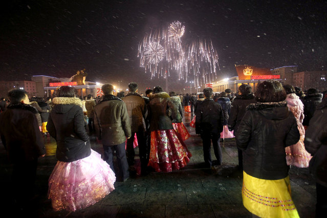 People watch a fireworks display from Kim Il Sung Square as they gather to celebrate a satellite launch in Pyongyang, North Korea, Monday, February 8, 2016. World leaders said the launch violated a U.N. ban on Pyongyang's use of ballistic missile technology. North Korea says the launch of a new Earth observation satellite, the Kwangmyongsong 4, or Shining Star 4, is part of a peaceful space program. (Photo by Jon Chol Jin/AP Photo)