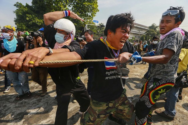 Anti-government protesters remove concrete barriers outside the Government House in Bangkok, Thailand, on December 3, 2013. Protesters swarmed into the Thai prime minister's office compound Tuesday as police stood by and watched, allowing them to claim a symbolic victory after three days of bitter clashes. (Photo by Wason Wanichakorn/Associated Press)