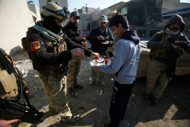 A civilian hands out tea to members of the Iraqi rapid response forces during a battle with the Islamic State militants in the Mithaq district of eastern Mosul, Iraq, January 5, 2017. (Photo by Khalid al Mousily/Reuters)