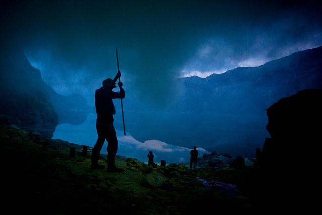 A miner uses a pole to extract sulphur from a pipe at the flow crater during the annual offering ceremony on the Ijen volcano. (Photo by Ulet Ifansasti/Getty Images)