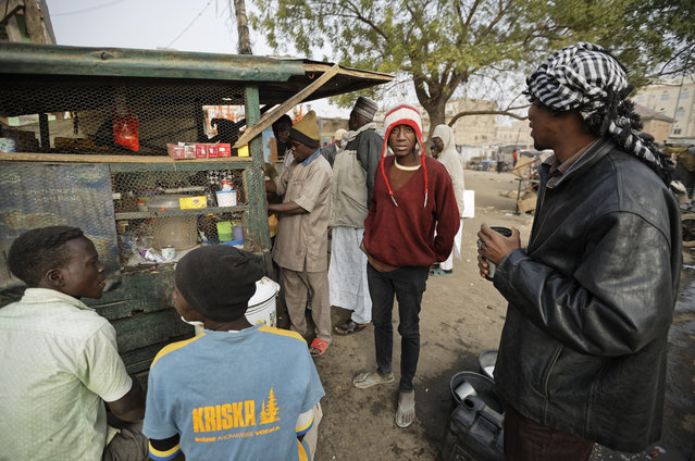 Newspaper distributors take hot drinks from a roadside stall in the morning next to a newspaper stand in Kano, in northern Nigeria Saturday, February 16, 2019. (Photo by Ben Curtis/AP Photo)