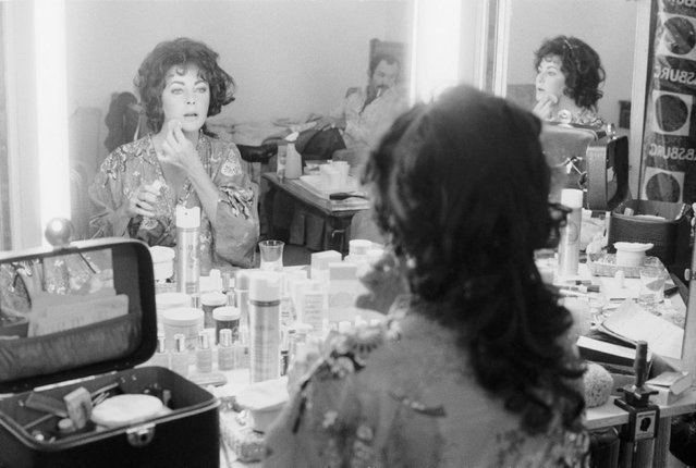 "Elizabeth Taylor, 1977. Elizabeth Taylor's beauty and glamour made her one of Hollywood's most legendary stars. Photographer Terry O'Neill captured this intimate shot of the icon applying her makeup in her dressing gown for ""A Little Night Music"" in 1977. (Photo by Terry O'Neill)"