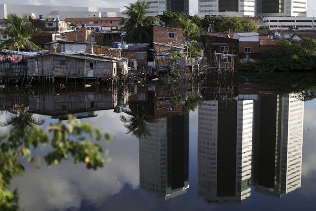"Luxury buildings are reflected in front of houses at a lake dwelling also known as or palafitte or ""Palafito"" in Recife, Brazil, March 1, 2016. (Photo by Ueslei Marcelino/Reuters)"