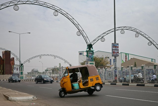 A supporter of President Muhammadu Buhari performs a stunt with an auto rickshaw as he celebrates in Kano, Nigeria on February 27, 2019. (Photo by Afolabi Sotunde/Reuters)