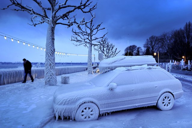 A man walks past an ice covered car on the frozen waterside promenade at Lake Geneva in the city Versoix, near Geneva on early February 5, 2012. (Photo by Fabrice Coffrini/AFP Photo)