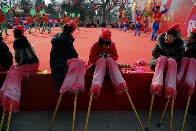 Performers on stilts try to stay warm as they wait their turn to go on the stage at the Longtan park during Chinese Lunar New Year celebration in Beijing, China January 29, 2017. (Photo by Damir Sagolj/Reuters)