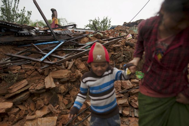 Local villagers walk amid debris at a devastated area following Saturday's earthquake, at Paslang village in Gorkha, Nepal April 28, 2015. (Photo by Athit Perawongmetha/Reuters)