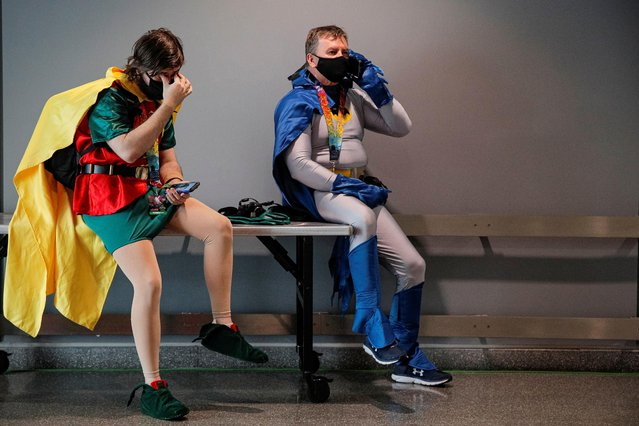 Attendees dressed as Batman and Robin take a break in a hallway during the 2021 New York Comic Con, at the Jacob Javits Convention Center in Manhattan in New York City, New York, U.S., October 7, 2021. (Photo by Brendan McDermid/Reuters)