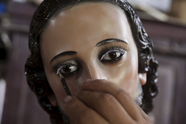 Jose Sabas Gomez pastes eyelashes to a statue of El Jesus Nazareno in his workshop in Apastepeque, El Salvador March 9, 2016. (Photo by Jose Cabezas/Reuters)
