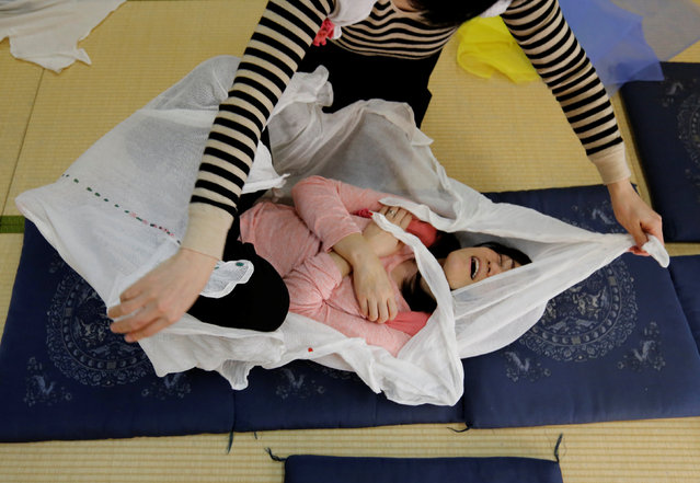 "A woman reacts after performing Otonamaki, which translates as ""adult wrapping"", a new form of therapy where people are wrapped in large swaddling cloth to alleviate posture problems and stiffness, at a session in Asaka, Saitama prefecture, Japan, February 4, 2017. (Photo by Toru Hanai/Reuters)"
