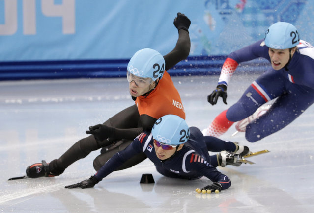 Sjinkie Knegt of Netherlands, left, and Park Se-Yeong of South Korea crash out as they compete in a men's 1500m short track speedskating final at the Iceberg Skating Palace during the 2014 Winter Olympics, Monday, February 10, 2014, in Sochi, Russia. (Photo by Bernat Armangue/AP Photo)