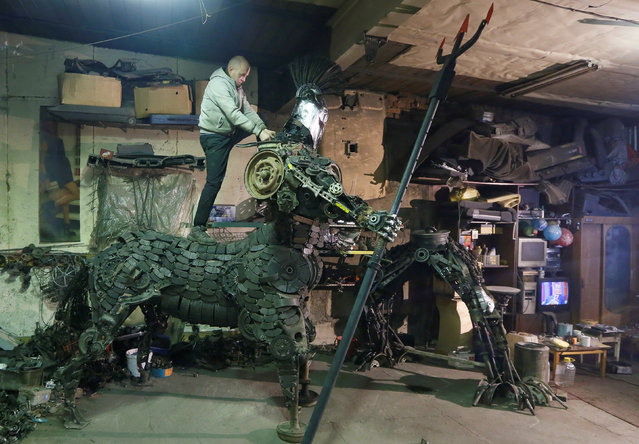 """Mechanic and welder Sergei Kulagin works on the """"Centaurus"""" sculpture, made of used car components, inside an automobile repair workshop in the Siberian town of Divnogorsk, Russia, February 9, 2017. (Photo by Ilya Naymushin/Reuters)"""