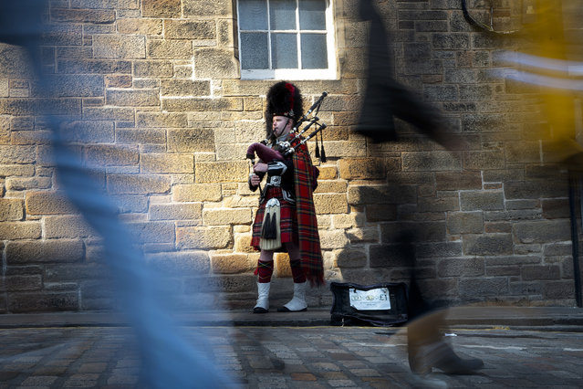 Members of the public walk past a piper on The Royal Mile in Edinburgh, Scotland on April 11, 2019. With Britain tearing its hair out over the Brexit confusion, Scotland's government is biding its time as it prepares for the ultimate prize – independence. (Photo by Andy Buchanan/AFP Photo)