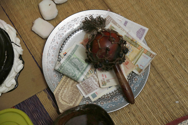 Money is placed on a plate beside an altar for the Afro-Cuban deity Yemaya at the home of Cuban santero Dagoberto Bocourt Miranda during a ceremony in Havana, Cuba, Thursday, May 7, 2015. The money is placed on the plate and the maraca is shaken while the person asks Yemaya for a wish. (Photo by Desmond Boylan/AP Photo)