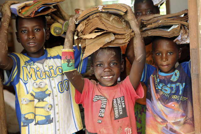 Children carry books damaged by the cyclone at a camp for displaced survivors of cyclone Idai in Dombe, about 280km west of Beira, Mozambique, Thursday, April 4, 2019. The Indian Ocean port of Beira, a city of 500,000, is where most of the more than 1,400 cases of cholera have been reported since the outbreak was declared a week ago in the aftermath of Cyclone Idai. Mozambican authorities have reported two deaths so far from the acute diarrheal disease, which can kill within hours if not properly treated. (Photo by Tsvangirayi Mukwazhi/AP Photo)