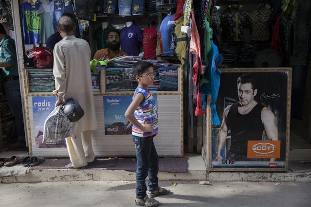 A photograph of Bollywood actor Salman Khan, right, part of an advertisement poster is displayed at a cloth store in New Delhi, India, Wednesday, May 6, 2015. One of India's biggest and most popular movie stars, Salman Khan, was sentenced to five years in jail Wednesday on charges of running over five men sleeping on a sidewalk and killing one in a hit-and-run case that has dragged for more than 12 years. (Photo by Tsering Topgyal/AP Photo)