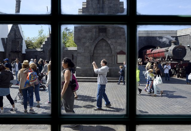 """Guests walk through Hogsmeade Village during a soft opening and media tour of """"The Wizarding World of Harry Potter"""" theme park at the Universal Studios Hollywood in Los Angeles, California in this picture taken March 22, 2016. (Photo by Kevork Djansezian/Reuters)"""