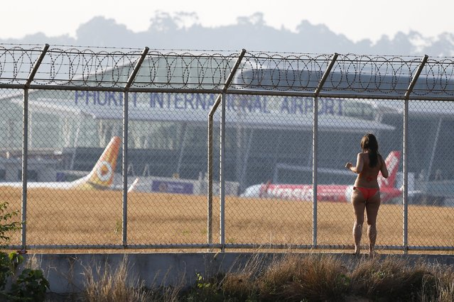 A tourist climbs on a fence of the Phuket International Airport in Phuket, Thailand March 17, 2016. (Photo by Athit Perawongmetha/Reuters)