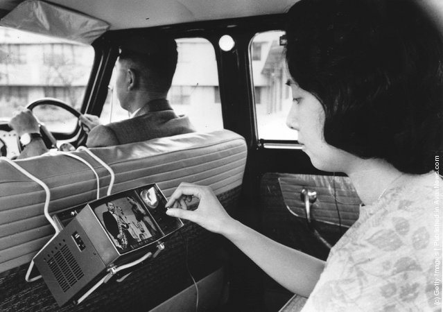 1963: A woman uses a new portable micro television, invented by the Japanese Sony Company, in the back of a car