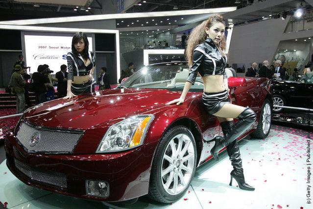Models poses next to a Cadillac XLR at the Seoul Motor Show